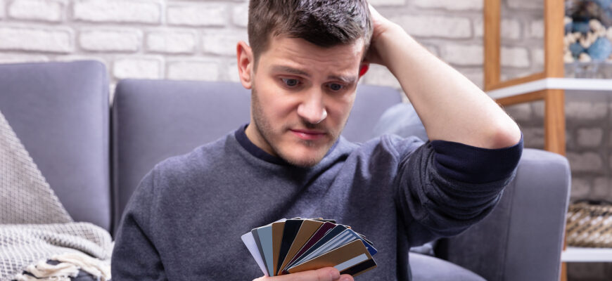 a man looking uncertain, head in hand, with his stack of credit cards wondering how many is too many credit cards to have
